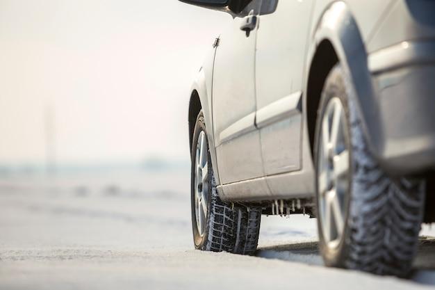 Het close-up van auto rijdt rubberband in diepe sneeuw.