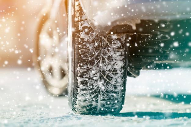 Het close-up van auto rijdt rubberbanden in diepe de wintersneeuw. transport en veiligheid.