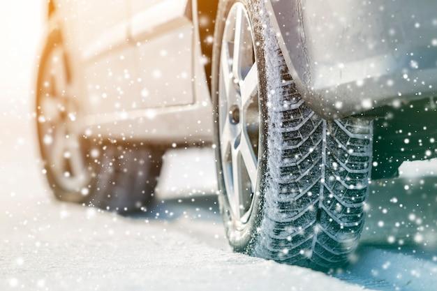 Het close-up van auto rijdt rubberbanden in diepe de wintersneeuw. transport- en veiligheidsconcept.