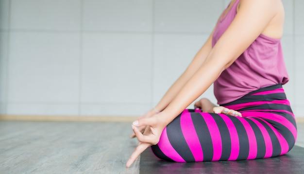 Het close-up van aziatische vrouwentraining het praktizeren yogatraining zette op roze kleren en oefent meditatie uit