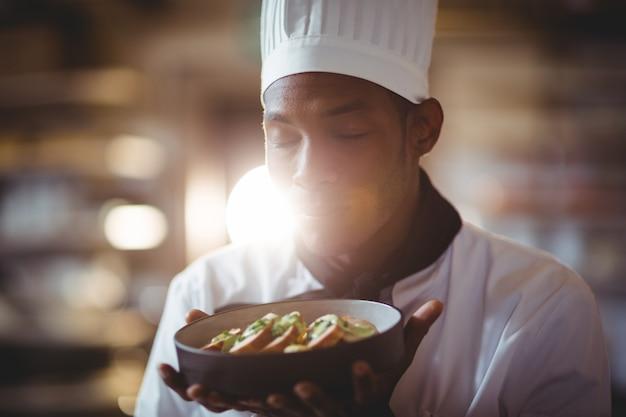 Het close-up van chef-kok met ogen sloot ruikend voedsel