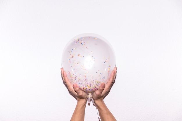 Het close-up van de hand die van een persoon transparante witte ballon met kleurrijk houden bestrooit tegen witte achtergrond