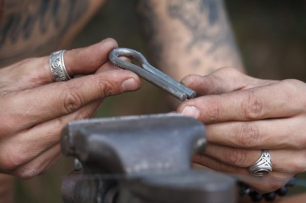 Het close-up van de hand van een man maakt een kaakharpen, khomuses, volksmuziekinstrumenten, selectieve nadruk