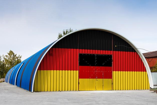 Het close-up van de nationale vlag van duitsland schilderde op de metaalmuur van een groot pakhuis het gesloten grondgebied tegen blauwe hemel. het concept van opslag van goederen, toegang tot een afgesloten ruimte, logistiek