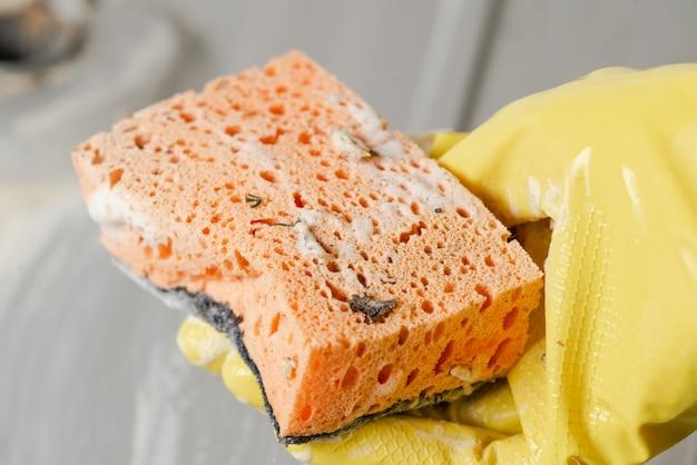 Het close-up van dient een gele handschoen met spons in.