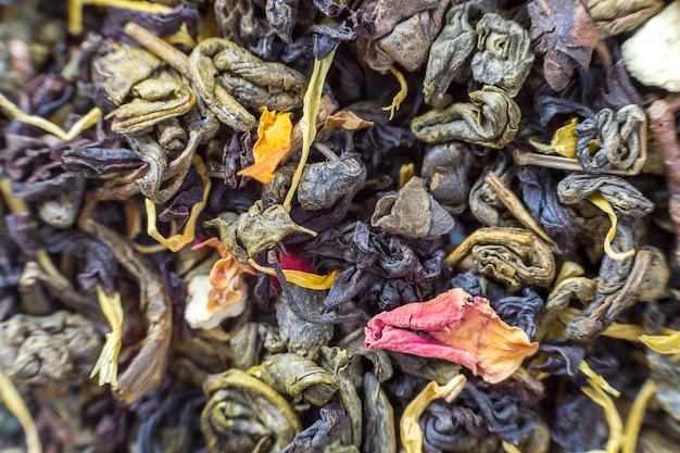 Het close-up van droge thee kruidenbloemblaadjes vat donkere donkere achtergrond samen. gezonde levensstijl, natuurlijke antioxidant drankje, aromatherapie concept.