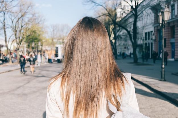 Het close-up van een mooi donkerbruin meisje met lang haar in een laag gaat rond de stad in de lente
