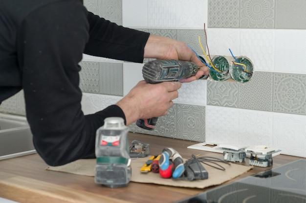 Het close-up van elektriciens overhandigt het installeren van afzet op muur met ceramisch