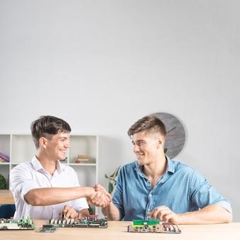 Het close-up van glimlachende mannelijke technicus die elkaar schudden dient dienstencentrum in
