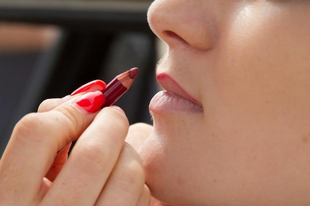 Het close-up van handen met rode manicure past make-up op jong vrouwengezicht toe, lipcontour door rood lippenpotlood