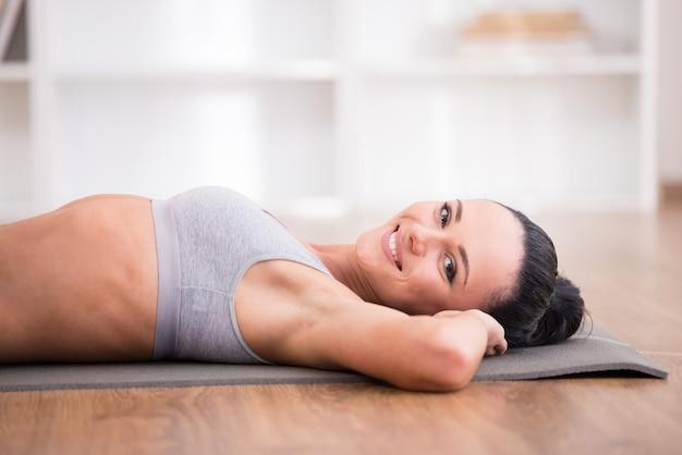 Het close-up van jonge sportieve vrouw ligt thuis op mat.