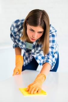Het close-up van jonge vrouw veegt wit bureau met gele stofdoek af
