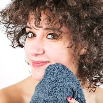 Het close-up van mooie jonge vrouw veegt gezicht met handdoek af