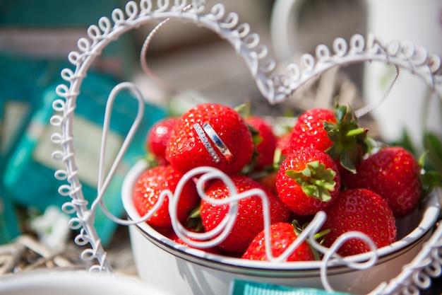 Het close-up van mooie trouwringen steekt van aardbeien in een vaas met een aardbeidia, selectieve nadruk uit