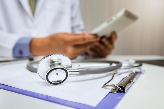 Het close-up van stethoscoop ligt op het klembord voor een arts.