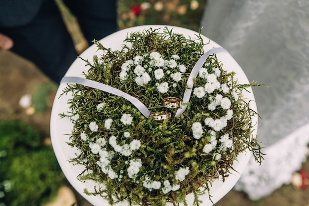 Het close-up van twee mooie gouden ringen ligt op het groene mos, selectieve nadruk