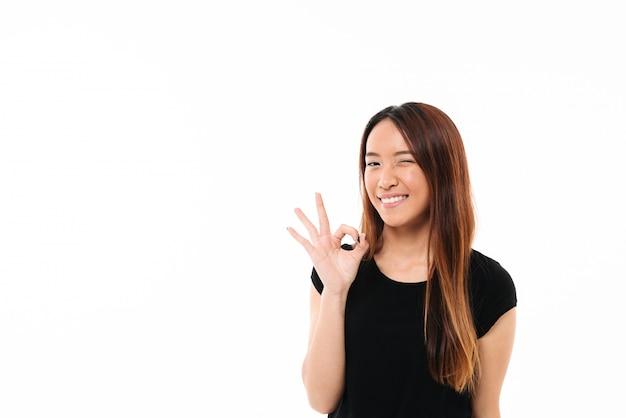 Het close-up van vrolijke vrij aziatische vrouw knipoogt en toont ok gebaar