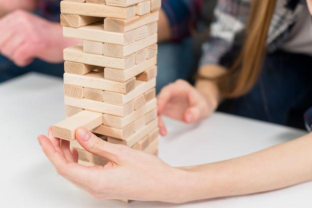 Het close-up van vrouw verwijdert zorgvuldig een blok van de het verwarren houten toren