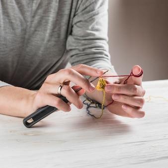 Het close-up van vrouwenhand breit wollen kleren over houten bureau