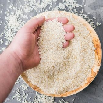 Het close-up van witte ongekookte rijst in mens overhandigt houten plaat