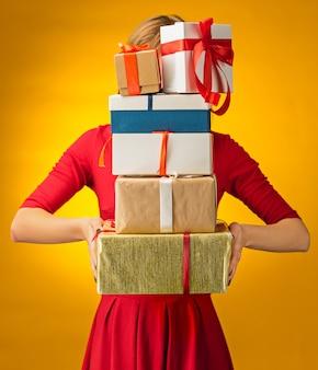 Het close-upbeeld van de handen van de vrouw met geschenkdozen op gele achtergrond