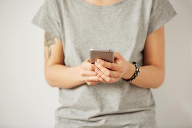 Het close-upbeeld van een tiener zoekt informatie in netwerk op mobiele telefoon