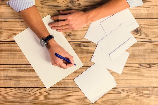 Het close-upboek van handen om nota's over een houten lijst te gebruiken.