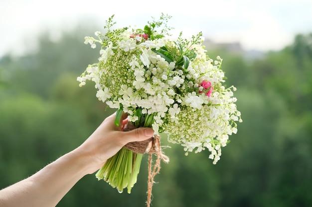 Het close-upboeket van verse bloemen nam en lelietje-van-dalen in vrouwenhand toe