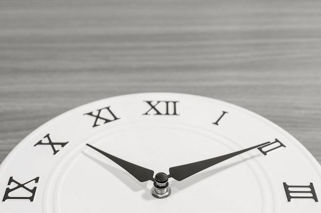 Het close-updeel van witte klok verfraait voor tien over tien uur op houten bureau