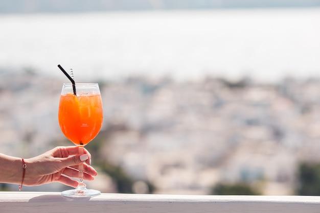 Het close-upglas met alcohol drinkt achtergrond in mooie oude mykonos