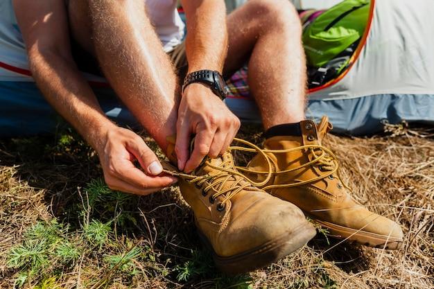 Het close-upmannetje bindt van schoenveters