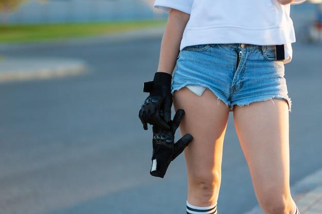 Het close-upmeisje houdt speciale handschoenen voor skateboardrit