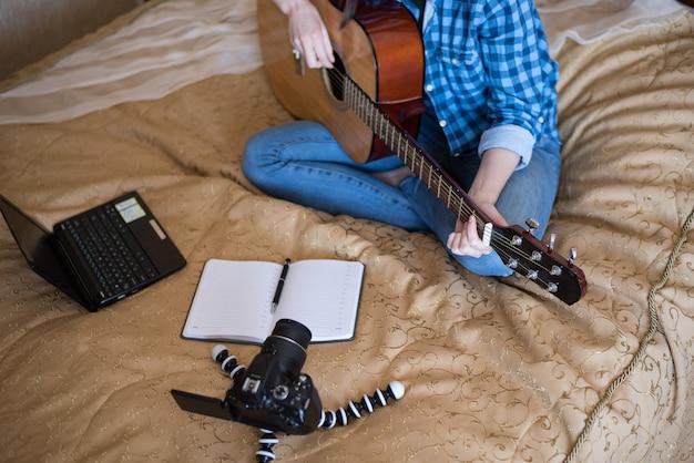 Het close-upmeisje in vrijetijdskleding op bed speelt akoestische gitaar en schrijft blog op camera dslr
