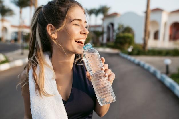 Het close-upportret opgewekte gelukkige jonge vrouw die met gesloten ogen aan zon glimlacht met een fles water. aantrekkelijke sportvrouw, genietend van de zomer, opleiding, thuiswerk, geluk.