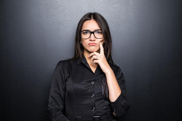Het close-upportret, sceptische, ernstige hogere jonge vrouw die verdacht kijkt, afkeuring op gezicht isoleerde zwarte muur.