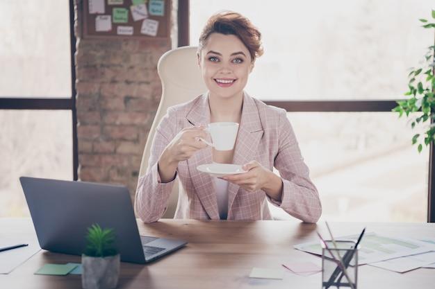 Het close-upportret van aardige aantrekkelijke vrolijke succesvolle bedrijfsdame drinkt koffie