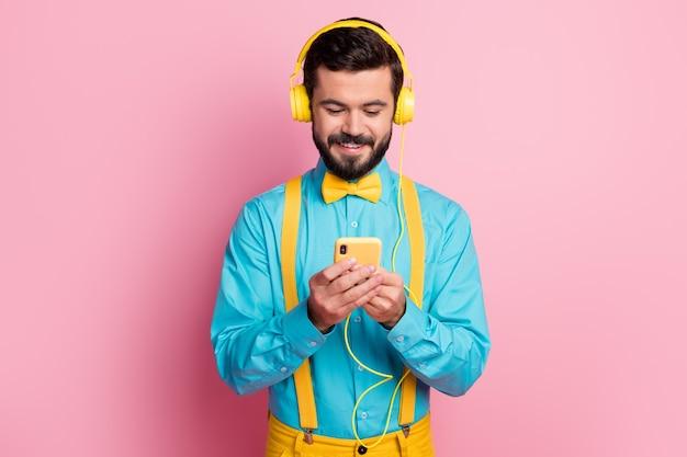 Het close-upportret van bebaarde kerel houdt telefoon die hoofdtelefoons draagt luisteren muziek