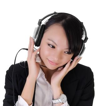 Het close-upportret van de bedrijfsdame luistert muziek door mp3-speler en hoofdtelefoon.