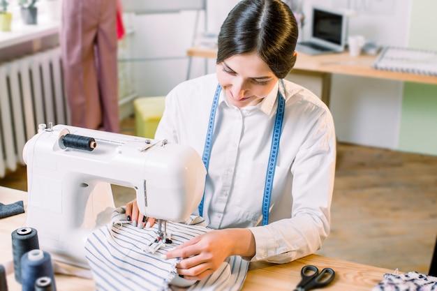 Het close-upportret van de jonge zitting van de vrouwennaaister en naait op naaimachine. mode, naaien van kleding, hobby naaien als een klein bedrijfsconcept