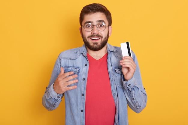 Het close-upportret van de verbaasde gebaarde mens met creditcard in handen, kijkt opgewekt, ontdekte over enorme hoeveelheid geld op kaart