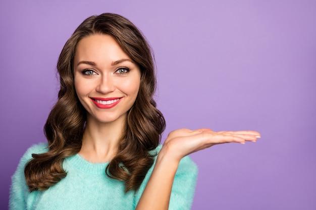 Het close-upportret van de vrij golvende dame houdt open arm adviserend nieuwigheidsproduct lage het winkelen prijs draagt ongedwongen blauwgroen pluizige pasteltrui.