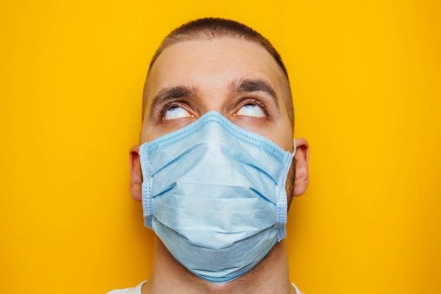 Het close-upportret van een aantrekkelijke jonge mens rolde zijn ogen in een beschermend masker op zijn gezicht. angst om ziek te worden, coronavirus concept. zonder leerlingen.
