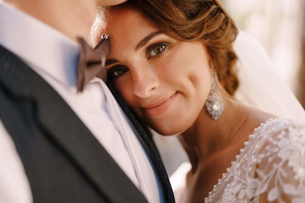 Het close-upportret van een bruid legde haar hoofd mooi op de borst van de bruidegoms