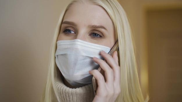 Het close-upportret van een jong meisje in medisch gezichtsmasker spreekt aan telefoon. gezondheid en veiligheid, quarantaine.