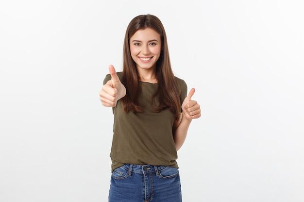 Het close-upportret van een mooie jonge vrouw die duimen tonen ondertekent omhoog