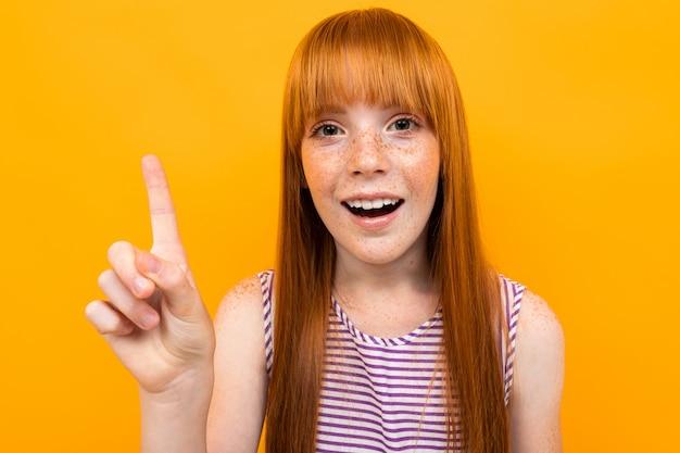 Het close-upportret van een roodharig meisje richt een vinger op de muur op een geel