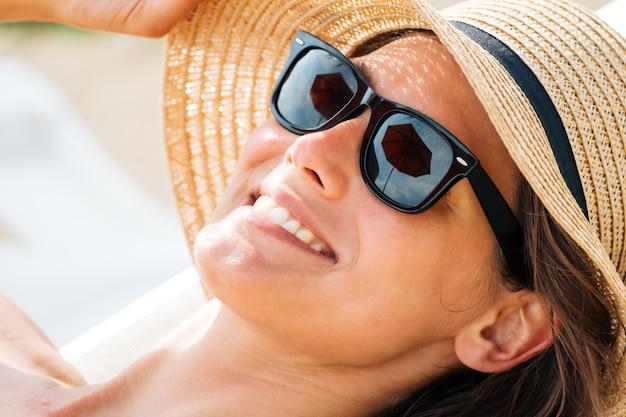 Het close-upportret van een wijfje verbergt haar gezicht van de zon onder een strohoed