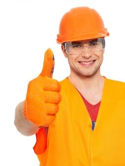 Het close-upportret van glimlachende vakman beduimelt omhoog teken in oranje beschermend uniform dat op witte achtergrond wordt geïsoleerd