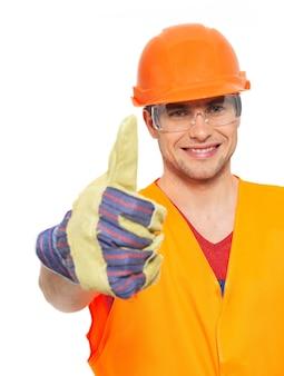 Het close-upportret van glimlachende vakman beduimelt omhoog teken in oranje beschermend uniform dat op witte muur wordt geïsoleerd
