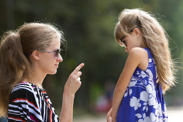 Het close-upportret van het profiel van gefrustreerde jonge blonde vrouw die aan jong klein kindmeisje spreekt.